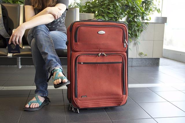 Sedící žena s kufrem u nohou