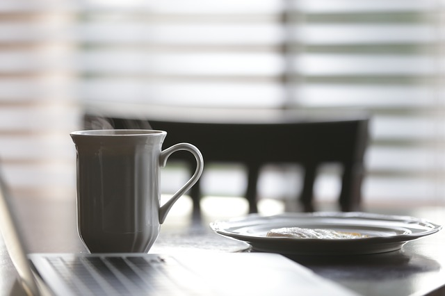 Detail hrnku s kávou, stojící na stole